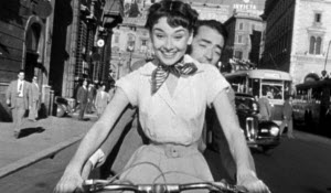 Audrey Hepburn and Gregory Peck riding a Vespa