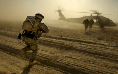 U.S. Army soldiers run towards a UH-60 Black Hawk helicopter